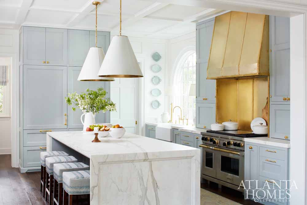 Pale blue and white marble kitchen with gold brass vent hood