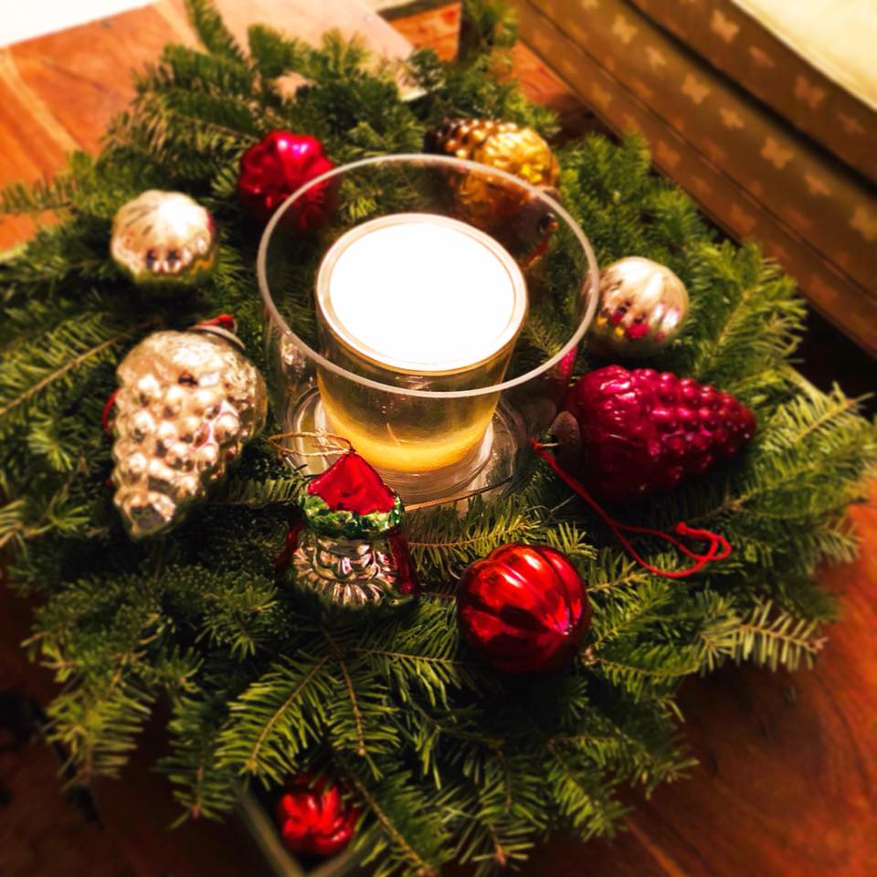 Evergreen wreath with red, silver and gold glass ornaments and a candle.
