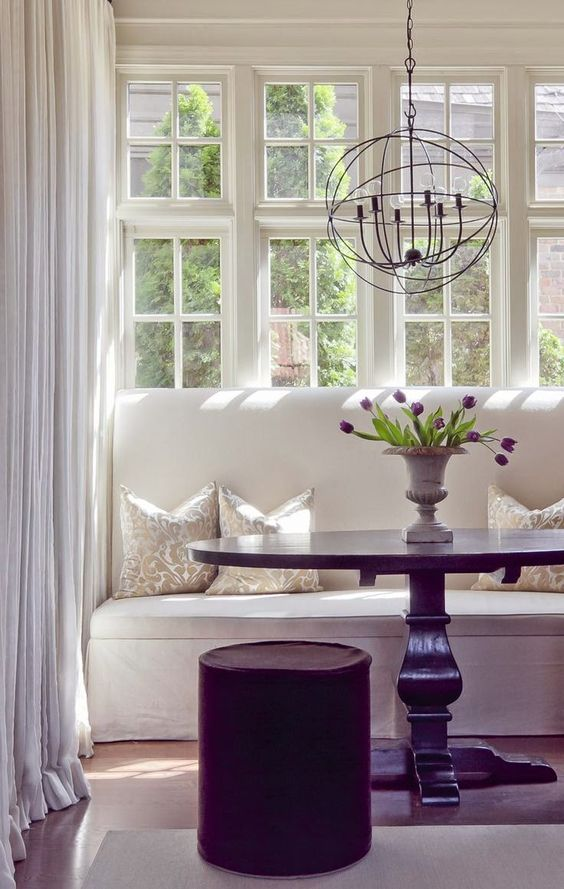 dining area orb pendant white drapery white dining banquettes settees